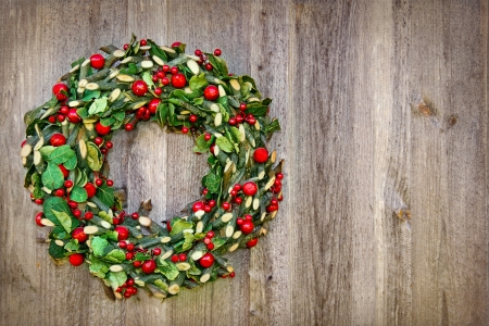 Rustic Christmas wreath hanging on a wooden vintage background with copy space