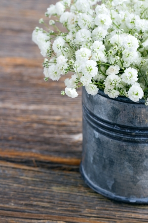 Bouquet of white baby's breath flowers (Gypsophila) on wooden rustic background