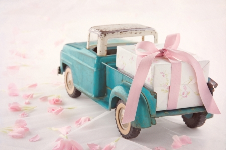 Old antique toy truck carrying a gift box with pink ribbon on romantic lace background and flower petals