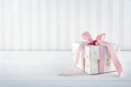 Floral pattern gift box tied with pink ribbon on white wooden background with copy space