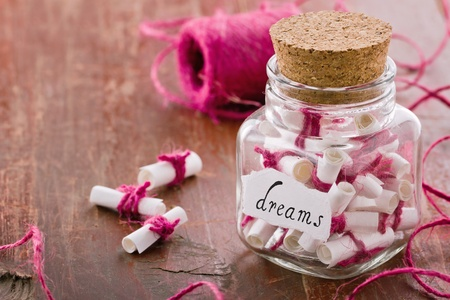 Dreams written on a white rolled paper in a glass jar on rustic vintage wooden background, dreaming optimism concept