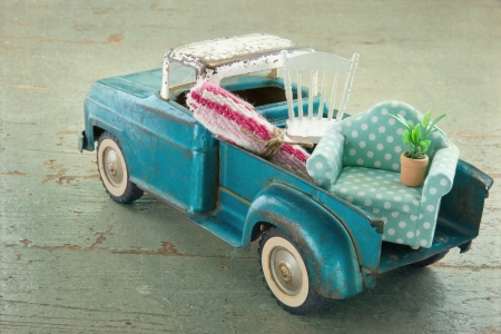 Old vintage toy truck packed with furniture - moving houses concept