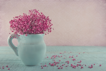 Pink dried baby's breath flowers in a blue jug on wooden background and vintage wallpaper
