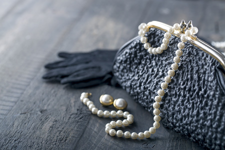 Photo pour Old elegant vintage handbag from the 1950's with luxury pearls and earrings on black background for copy space - image libre de droit