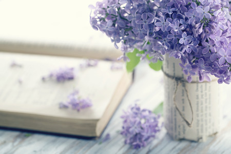 Bouquet of purple lilac spring flowers with an open book and vintage hazy editing