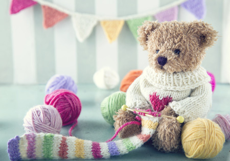 Teddy bear in a woolen sweater knitting a striped scarf with colorful balls of yarn