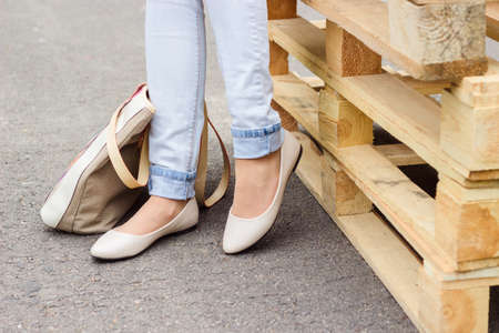 Woman's legs in jeans and white ballet flat shoes with beige bag, standing near wooden palettes