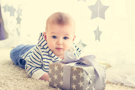 Photo pour Portrait of a cute baby boy with big blue eyes wearing jeans and striped hoodie sweater lying in front of his present in wrapped box with ribbon. Birthday or Christmas presents concept - image libre de droit