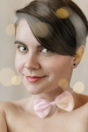 Young woman face with lights bokeh on foreground. Christmas style portrait of the young girl with a pink bow tie on her neck