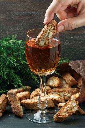 Female hand dip traditional Italian cantuccini biscuits into a glass of sweet Vin Santo wine over wooden background