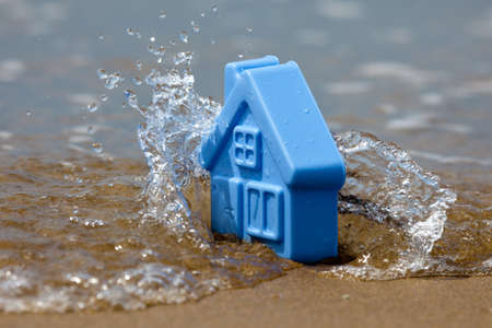 Blue plastic toy house on the sand covered with the waves, forming the spray - a metaphor for the sudden flooding