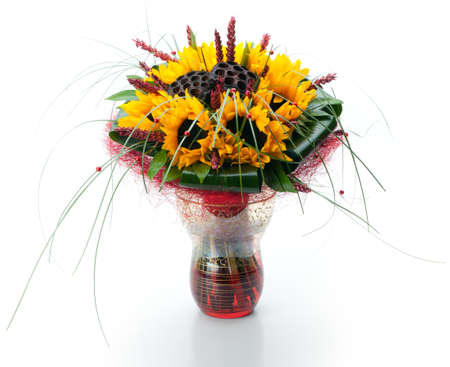 Festive composite bouquet of sunflowers and long grass in a glass vase on a white background