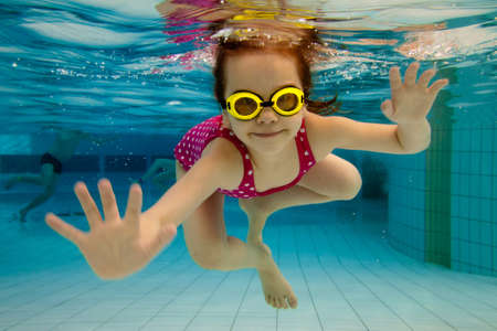 Photo pour The little girl in the water park swimming underwater and smiling - image libre de droit