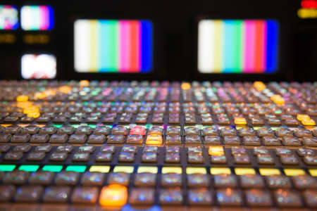 Photo pour Television gallery with selective focus on the foreground vision mixing panel and TV monitors out of focus in the background  - image libre de droit