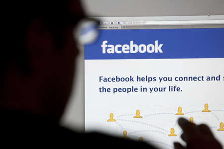 Bath, United Kingdom - May 4, 2011: Close-up of the Facebook homepage displayed on a LCD computer screen with silhouette of a man