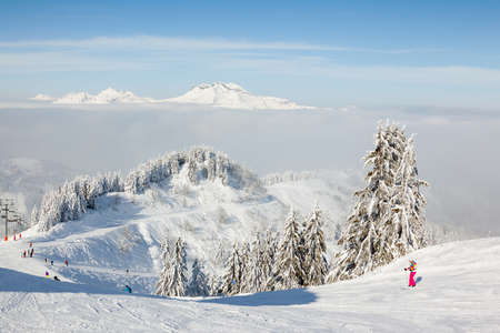 MORZINE, FRANCE - FEBRUARY 06, 2015: Skiers and snow boarders on Le Ranfoilly mountain peak in Les Gets ski resort in the Portes du Soleil ski area.