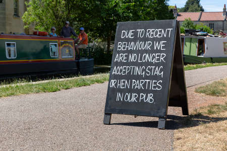 Foto de BATH, UK - JUNE 30, 2018 : A chalkboard sign outside a public house on the Kennet and Avon Canal notifying stag and hen parties they are no longer allowed entry due to recent bad behaviour. - Imagen libre de derechos