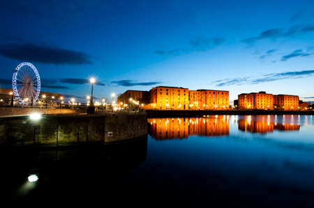 Liverpool Albert dock cityscape at night with view of Maritime Museum and Ferris Wheel