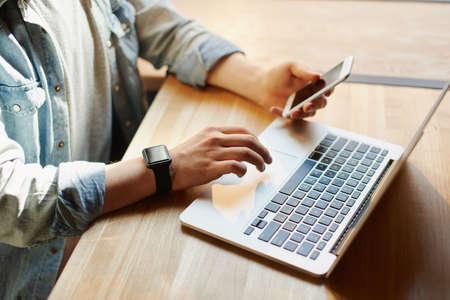 Foto de Young man works on the laptop in the cafe. - Imagen libre de derechos