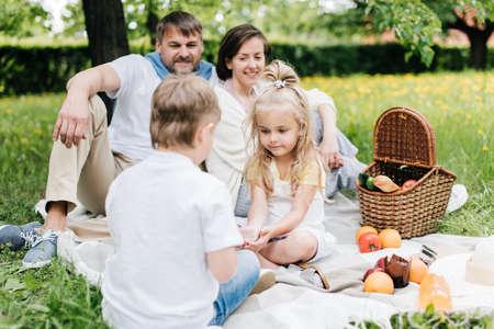 Photo pour Kids communicating with each other at family picnic. - image libre de droit