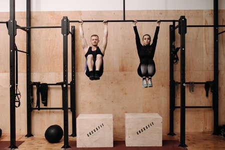 Man and woman doing exercise on horizontal bar