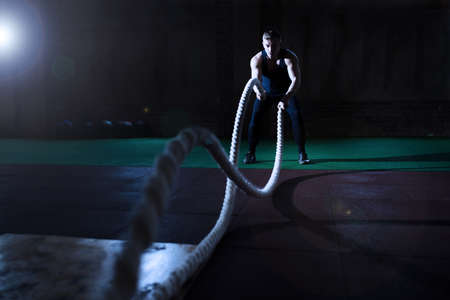 Athletic man doing some crossfit exercises with a rope in gym