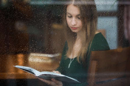 Photo pour Woman reading book in the cafe, view through wet window at rainy day - image libre de droit