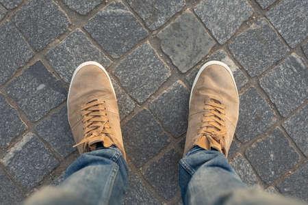 Photo pour POV of male gumshoes on paving slabs, view from above - image libre de droit