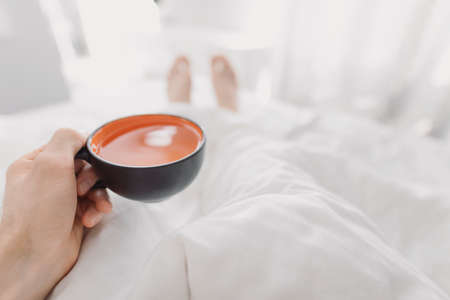 POV, man drinking morning tea in a bed