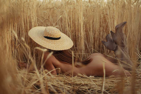 Photo for Naked woman lying on a field with hat, nudes at nature - Royalty Free Image