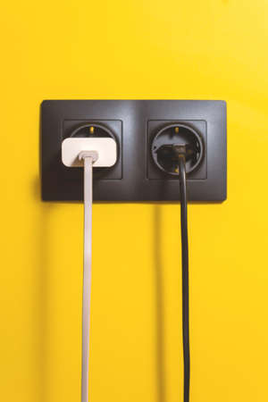 Photo pour Doubled black socket on yellow wall. Conceptual photo of electricity use in today's life of every person. Different color wires. - image libre de droit