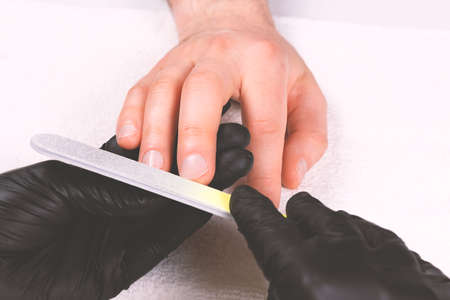 Photo pour Manicurist in black gloves files man's nails with single-use nail file. Young businessman doing manicure. Take care of yourself. Modern way of life. - image libre de droit