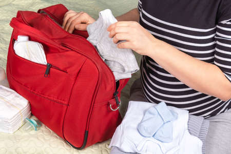 Photo pour Unrecognizible pregnant caucasian woman in striped t-shirt packing big red diaper bag to maternity hospital. Diapers, grey plaid, socks, bottle and bodysuit for newborn baby. - image libre de droit