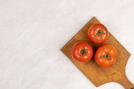 Photo pour Fresh whole ripe tomatos on grey marble background with copy space. Summer organic vegetable for salad - image libre de droit