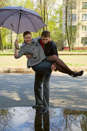 Couple walk across the puddle. Man carries woman on own hands. She is with grey umbrella.