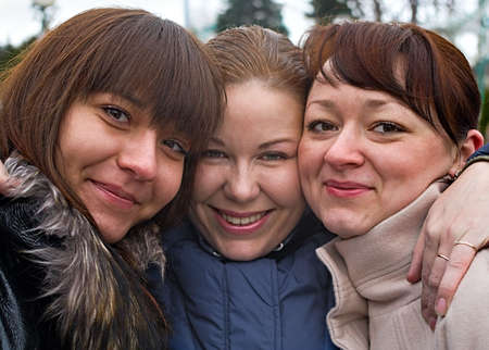 Three women stay together with another. Portraits. They are caucasian. Friends.