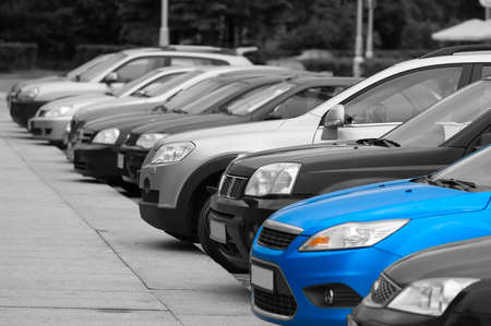 Black-and-white cars are on the parking and only one blue colored automobile.