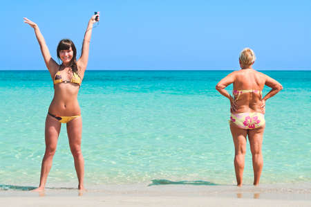 Young sexy girl and senior women standing on sandy beach near the sea.