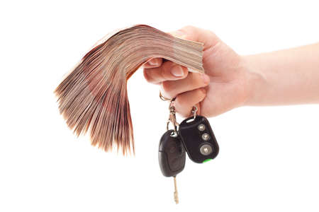 Human hand with bundle of money and automobile keys isolated on white background