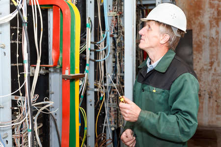 Mature electrician working in hard hat with screwdriver