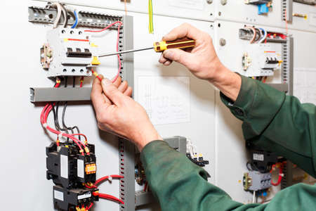 Electrician`s hands working with screwdriver in cables and wires.