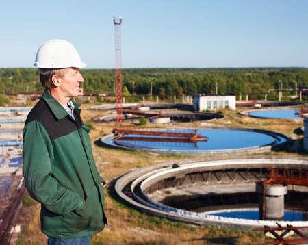 Mature man manual worker in white hardhat near sewage treatment basin