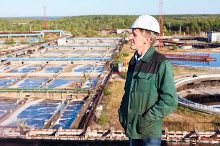 Mature man manual worker in white hardhat near sewage treatment plant