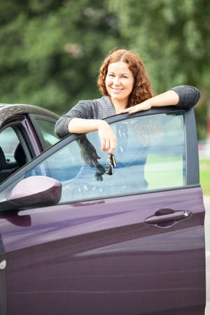 Beautiful bright brunette with keys standing near just bought car