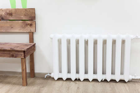 White iron radiator of central heating is near wooden bench in room