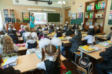 ST. PETERSBURG, RUSSIA - SEP, 1, 2014: First-grade students and teacher are in school classroom at first lesson. Children go back to school at first time in September