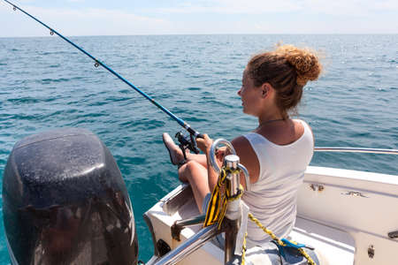 Photo pour Young European woman has angling excursion, sitting in boat with spinning rod - image libre de droit