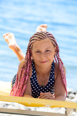 Photo pour Pretty Caucasian girl with pink dreadlocks hairstyle lying on yellow sunbed at sunny day, looking at camera - image libre de droit