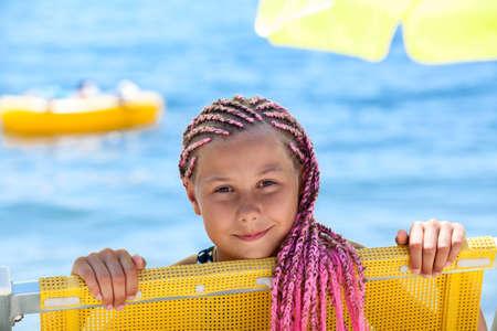 Foto de Face of happy pre-teen Caucasian girl with pink dreadlocks hairstyle looking out from yellow sun lounger, sunny coastline - Imagen libre de derechos