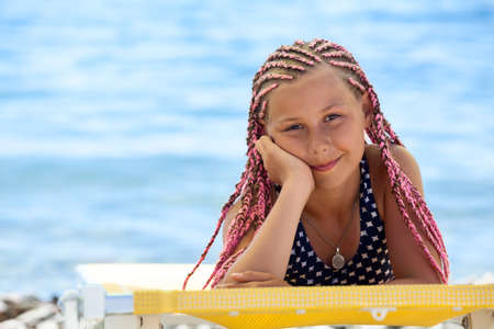 Foto de Portrait of preteen Caucasian girl with pink dreadlocks hairstyle tanning on beach on seacoast - Imagen libre de derechos